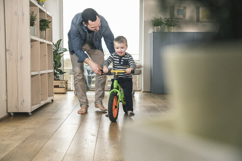 Father helping son riding with a balance bicycle at home - UUF16873