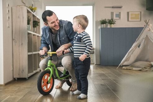Father helping son riding with a balance bicycle at home - UUF16876