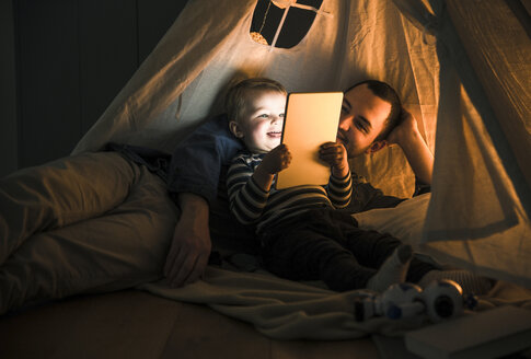 Father and son sharing a tablet in a dark tent at home - UUF16879