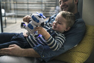 Father and son playing with a toy robot at home - UUF16900