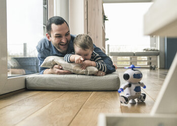 Excited father and son lying on a mattress at home watching a toy robot - UUF16906
