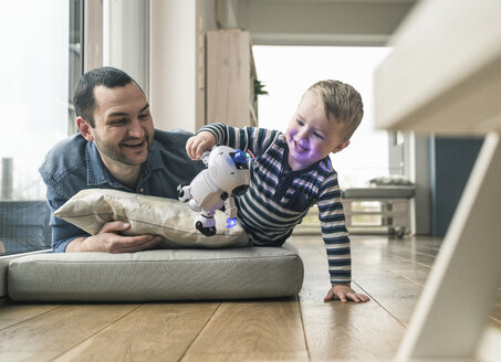 Excited father and son lying on a mattress at home watching a toy robot - UUF16909