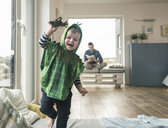 Happy boy in a costume playing with toy figure at home - UUF16918