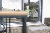 Happy boy in a costume standing at terrace door at home - UUF16921