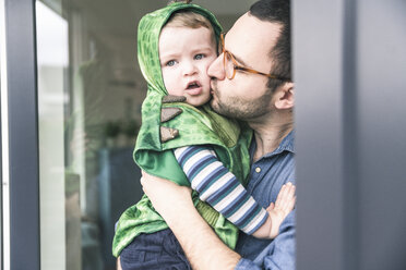 Father kissing son in a costume at terrace door at home - UUF16927