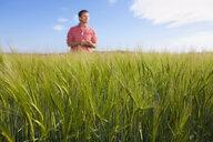 Farmer standing in barley field - JUIF00799