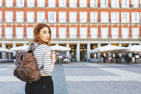 Spain, Madrid, Plaza Mayor, portrait of redheaded young woman with backpack in the city - WPEF01450