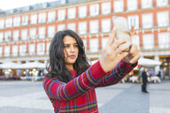 Spain, Madrid, Plaza Mayor, portrait of woman taking selfie with smartphone - WPEF01453
