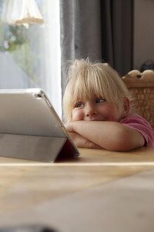 Portrait of blond little girl using digital tablet at home - GAF00101