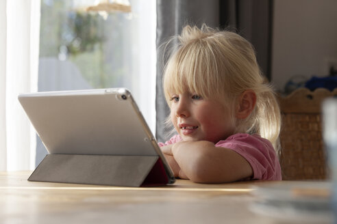 Portrait of blond little girl using digital tablet at home - GAF00104