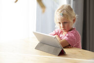 Portrait of blond little girl using digital tablet at home - GAF00107