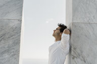 Man wearing white shirt leaning against marble column looking up - AFVF02645