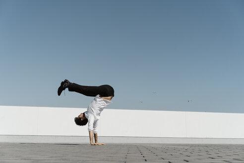 Artist doing handstand on roof terrace - AFVF02663