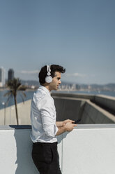Profile of businessman listening music with headphones and smartphone on roof terrace - AFVF02675