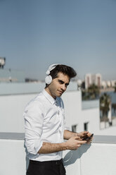Spain, Barcelona, portrait of businessman listening music with headphones and smartphone on roof terrace - AFVF02678