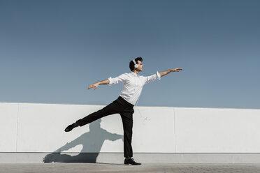 Ballet dancer with headphones practising on roof terrace - AFVF02681