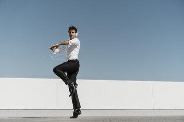 Ballet dancer with headphones practising on roof terrace - AFVF02690