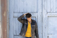 Smiling man wearing leather jacket standing in front of lightblue wooden door - AFVF02702