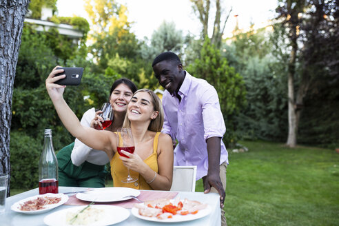 Friends having fun at a summer dinner in the garden, taking selfies - ABZF02285