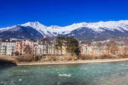Austria, Tyrol, Innsbruck, colored buildings along the Inn river with snow-capped Alps in background - FLMF00173