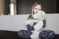 Portrait of smiling little girl wearing pyjama with floral design holding white teddy bear - EYAF00077