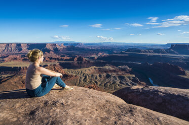 USA, Utah, Woman at a overlook over the canyonlands and the Colorado river from the Dead Horse State Park - RUNF01691