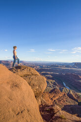 USA, Utah, Woman at a overlook over the canyonlands and the Colorado river from the Dead Horse State Park - RUNF01694
