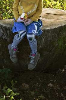 Low section of girl with an apple sitting on a tree stump - GAF00112