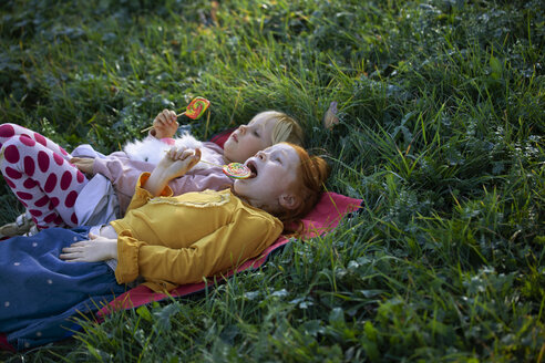 Two sisters lying in a field holding lollipops - GAF00115
