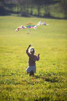 Little girl running in field with kite - GAF00118