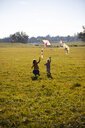 Two girls running in field with kite - GAF00121