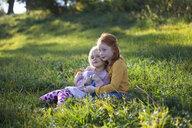 Two sisters cuddling in field - GAF00127