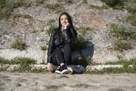 Portrait of smiling young woman sitting on curb - GIOF05963