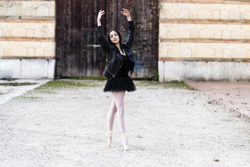 Italy, Verona, portrait of Ballerina dancing in the city wearing leather jacket and tutu - GIOF05990