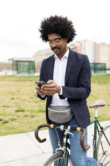 Spain, Barcelona, businessman on bicycle using cell phone in the city - VABF02253