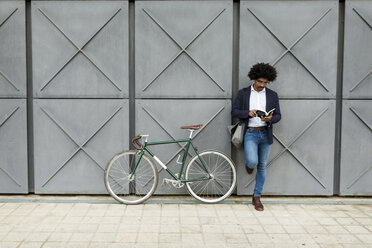 Businessman with bicycle leaning against a wall reading book - VABF02262