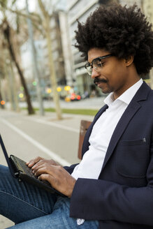 Spain, Barcelona, businessman in the city sitting on bench using laptop - VABF02283