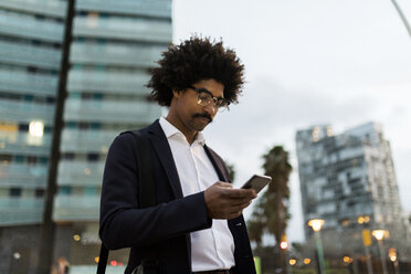 Spain, Barcelona, businessman in the city using cell phone at dusk - VABF02316