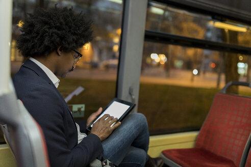 Spain, Barcelona, businessman in a tram at night using tablet - VABF02322