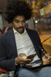 Spain, Barcelona, businessman in a tram at night using cell phone - VABF02328