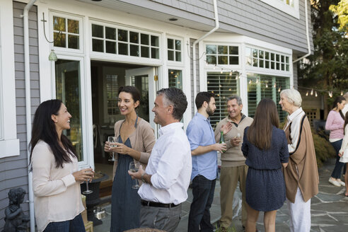 Friends and family talking drinking wine on patio - HEROF33161