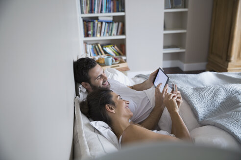 Couple using cell phone and digital tablet bed - HEROF33167