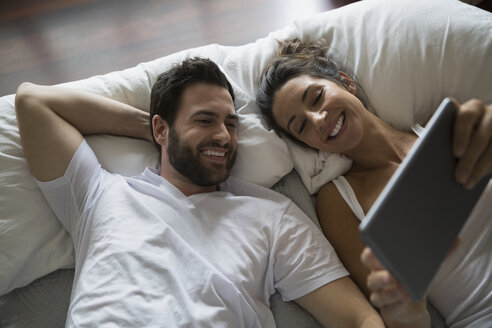 Couple using digital tablet on bed - HEROF33170