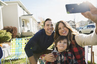 Family taking selfie in sunny sunny front yard - HEROF33218