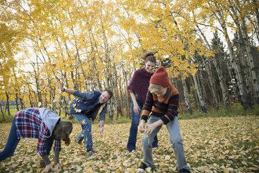 Family playing throwing autumn leaves - HEROF33251