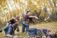 Family playing throwing autumn leaves - HEROF33254