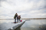 Family fishing on lake jetty - HEROF33257