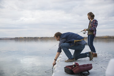 Father and daughter catching fish with net on lake jetty - HEROF33266