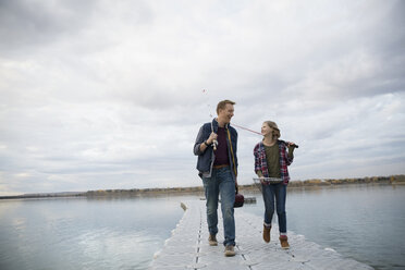 Father and daughter fishing on lake jetty - HEROF33269