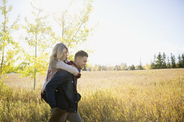 Couple piggybacking in sunny field - HEROF33272